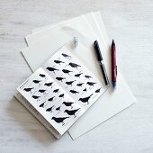 Pens next to book containing various illustrations of birds