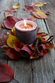 Candle in wreath of autumnal cherry leaves on rustic wooden surface