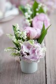 Posies of hydrangeas, lily-off-the-valley and peonies in white ramekins
