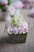 Arrangement of lily-of-the-valley and hydrangeas in small, vintage container