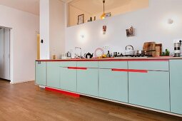 Long counter with red accents in open-plan kitchen with oak floor and aperture in wall above wall lamps