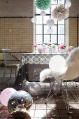 Feminine, romantic party decorations with light reflecting from disco ball, suspended pompons and flowers on table in disused factory with industrial windows