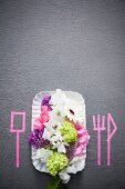 Place setting with summer flowers and silhouettes of cutlery marked on grey surface with pink washi tape