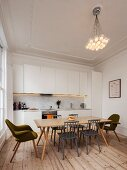 Simple, white fitted kitchen in renovated period apartment with wooden floor, retro-style dining area and designer pendant lamp hanging from ceiling with stucco frieze