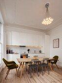 Schlichte weiße Einbauküche in renoviertem Altbau mit Dielenboden, Eßplatz im Retrostil und Designer-Pendelleuchte an Decke mit Stuckleiste