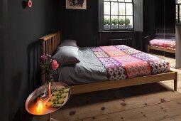 Schlafzimmer schwarz gestrichen mit Holzbett und bunter Tagesdecke, Spiegelschrank, Tabletttisch mit beleuchteter Lampe und Rosensträußchen