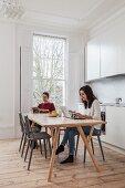 Junges Paar in weißer Altbau-Wohnküche mit Sprossenverglasung und Dielenboden am Esstisch lesend und am Laptop beschäftigt