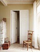 Antique wooden chair in front of double doors in rustic foyer