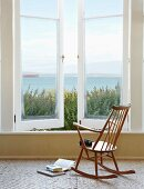 Simple wooden rocking chair in front of window with sea view