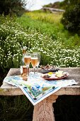 Picnic and sparkling wine on stone bench with antique Greek elements in the country