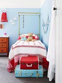 Stacked pale blue and red vintage suitcases at foot of child's bed with canopy frame in girl's bedroom painted pale blue