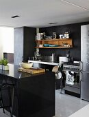 Black island unit opposite workbench-style kitchen counter and wooden shelves on dark wall