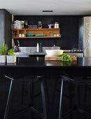 Black, designer bar stools at black counter; wooden shelves on dark wall in background