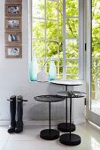 Black, three-piece set of tables below lattice window with view into garden