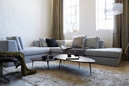 Pale grey corner sofa and fifties-style coffee table set on flokati-style rug in corner in front of lattice windows