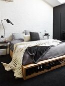 White blanket with pattern of holes on DIY bed with integrated shoe rack in rustic interior with whitewashed brick wall