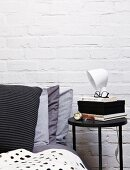 Black side table and stacked scatter cushions in shades of grey on bed against whitewashed brick wall