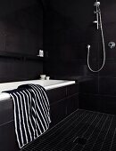 Black and white striped towel on edge of bathtub in black-tiled designer bathroom