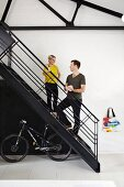 Woman and man on black metal staircase with bicycle stored below in loft apartment