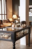 Ornaments in display-case coffee table with turned legs, vintage birdcage and mounted, stuffed armadillo in front of pillar in open-plan, country-house-style interior