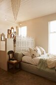 Romantic bedroom with pale green cushion platform bed and artistic white screen against partition separating ensuite bathroom with gallery of nostalgic mirrors