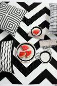 Cushions with graphic, black and white patterns and plate of red melon slices against bold, zigzag background