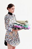 Woman wearing colourful pixelated dress holding stack of patterned fabrics