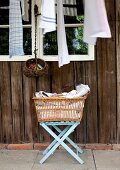 Laundry basket on folding stool outside rustic wooden cabin