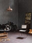 Vintage motorbike, wire chair and rustic wooden crates in corner of room