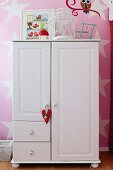 White wardrobe with heart-shaped pendant against pink-painted wall with pattern of stars