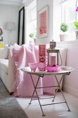 Pink champagne goblets and candle lantern on tray table next to sofa with cosy, pastel pink blanket