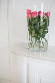 Pink roses inside tall glass vase on white dresser