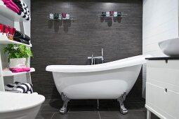 Free-standing, clawfoot bathtub in bathroom with white and charcoal tiles and towels on ladder shelves to one side