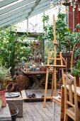 Easel in front of potted plants and gardening utensils in greenhouse