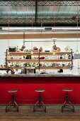 Bar in former workshop with red bar counter, vintage swivel stools and long shelves of bottles