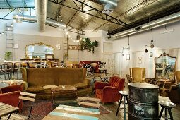 Private club with comfortable, vintage furnishings below metal ceiling in former workshop