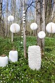 White lanterns of various shapes in thin woodland carpeted with flowering wood anemones