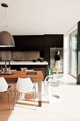 Modern, open-plan kitchen with brown cupboards, floor-to-ceiling glass wall & dining area