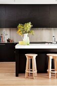 Kitchen with brown cupboards & island counter with wooden stools