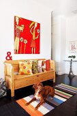 Dog lying on striped rug in front of rustic bench with scatter cushions below artwork