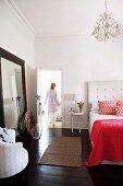 Double bed with upholstered headboard in bedroom with dark wooden floor