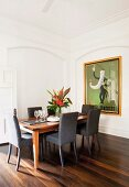 Chairs with grey upholstery around flower arrangement on elegant dining table; large, framed retro poster on wall within stucco panel