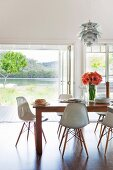 Classic, white shell chairs around wooden table in modern interior in front of open terrace door with view of lake