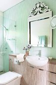 Washstand with protruding sink below ornate mirror on wall with mosaic tiles; glazed shower area in corner