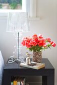 Bouquet of red flowers in vase next to transparent, plastic table lamp on dark bedside table