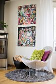 Scatter cushions on swivel easy chair on round long-pile rug in front of comic-style artworks on wall