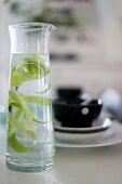 Glass carafe of water with lime peel in front of place setting with black bowl