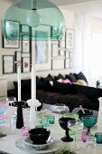 Various goblets and glasses of different colours on table below pendant lamp with green transparent lampshade