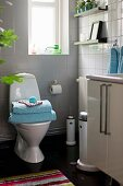 White-tiled bathroom with stack of towels on toilet below window