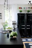 Dishes on counter with black worksurface and glossy, black, fifties-style fridges in background